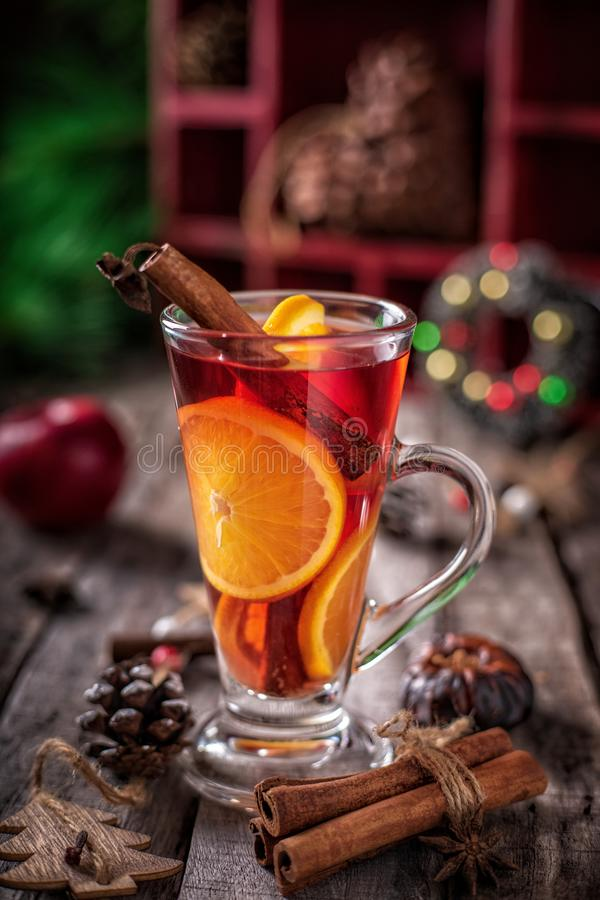 GGlass of Christmas mulled red wine with spices and fruits on a wooden background royalty free stock photo