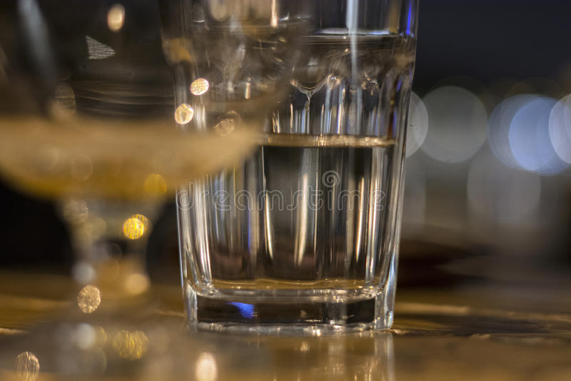 Gglass of water half-full standing on wooden table. Close-up picture of a glass of water which is half-full standing on a brown wooden table at Christmas Eve royalty free stock images