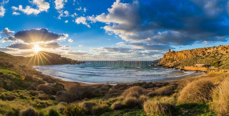 Ghajn Tuffeha, Malta - vista panorámica de la playa de Ghajn Tuffieha en la puesta del sol en un día de verano precioso con el ci imagen de archivo