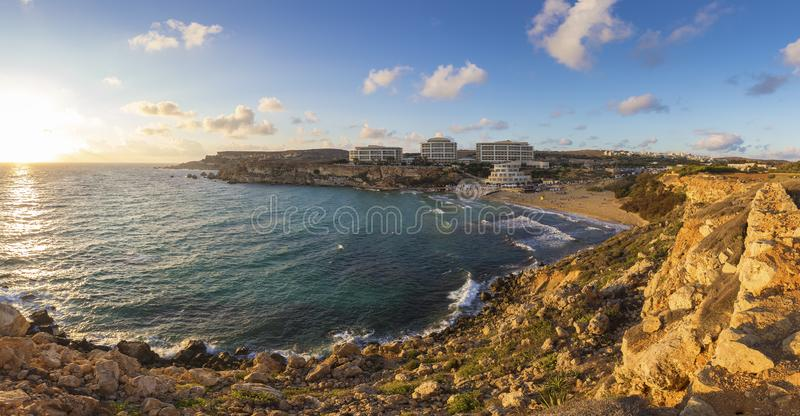Ghajn Tuffieha, Мальта - панорамный взгляд горизонта золотого залива, ` s Мальты большинств красивый песчаный пляж на заходе солн стоковое изображение rf