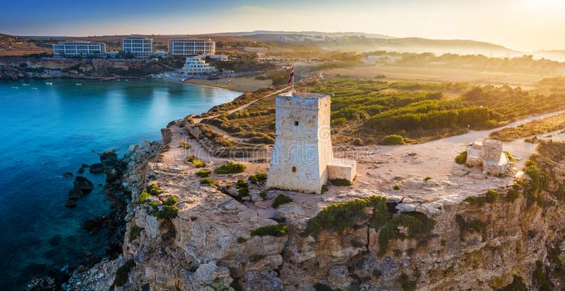 Ghajn Tuffieha, Malta - salida del sol hermosa en la torre del reloj de Ghajn Tuffieha con la playa de oro de la bahía imagenes de archivo