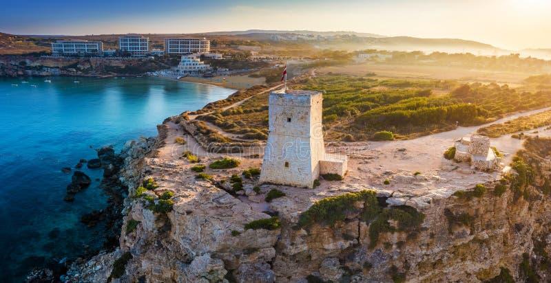 Ghajn Tuffieha, Malta - schöner Sonnenaufgang am Uhr-Turm Ghajn Tuffieha mit goldenem Buchtstrand stockbilder
