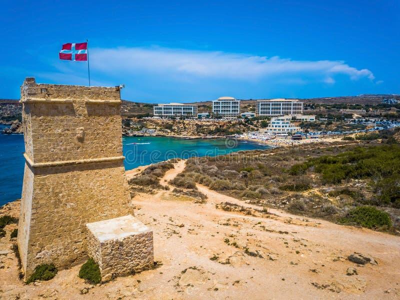 Ghajn Tuffieha, Malta - schöner Uhr-Turm Ghajn Tuffieha und goldene Bucht setzen an einem hellen Sommertag auf den Strand lizenzfreies stockbild
