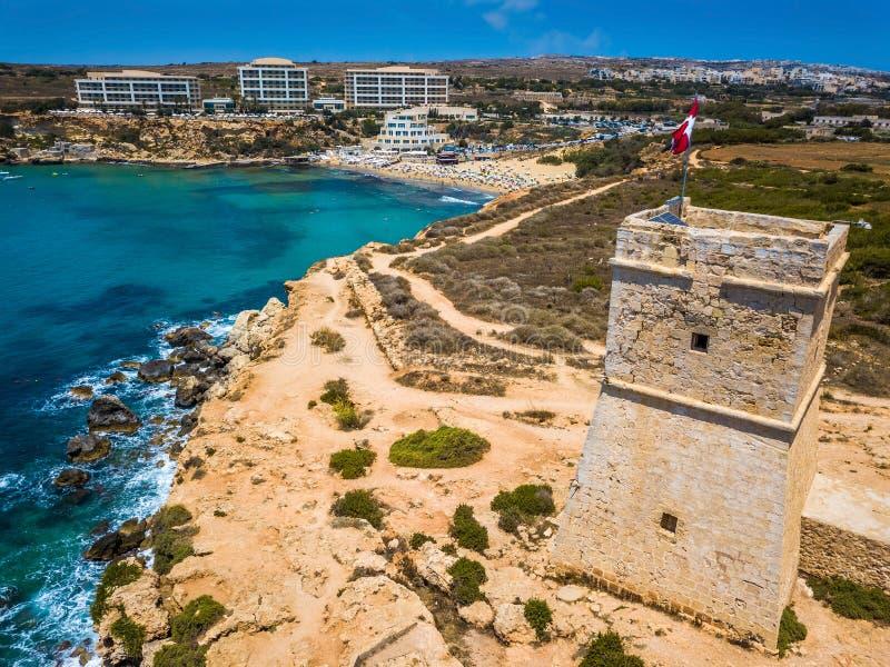 Ghajn Tuffieha, Malta - schöner Uhr-Turm Ghajn Tuffieha und goldene Bucht setzen an einem hellen Sommertag auf den Strand stockbilder