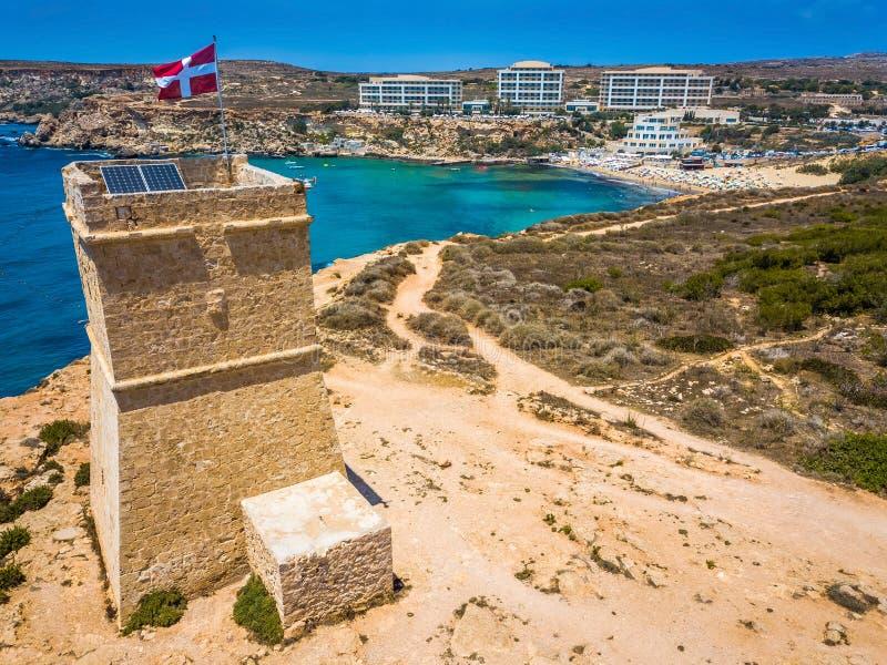 Ghajn Tuffieha, Malta - a torre bonita do relógio de Ghajn Tuffieha e a baía dourada encalham em um dia de verão brilhante imagem de stock royalty free