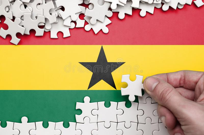 Ghana flag is depicted on a table on which the human hand folds a puzzle of white color stock image