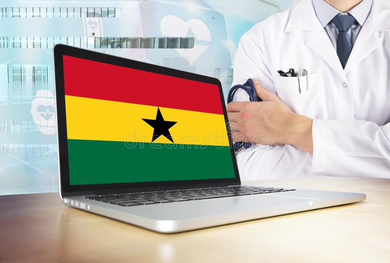 Ghana healthcare system in tech theme. Ghanaian flag on computer screen. Doctor standing with stethoscope in hospital. Cryptocurrency and Blockchain concept stock photos