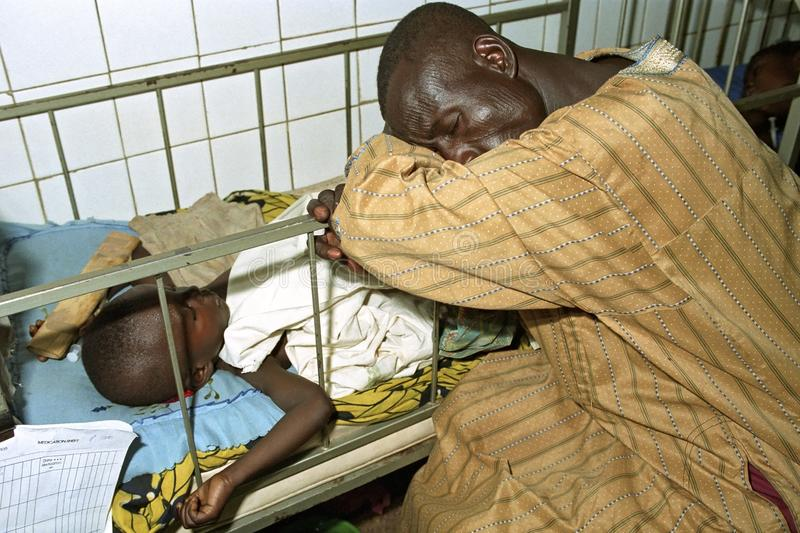 Ghanaian father is guarding his sick child in hospital royalty free stock photography