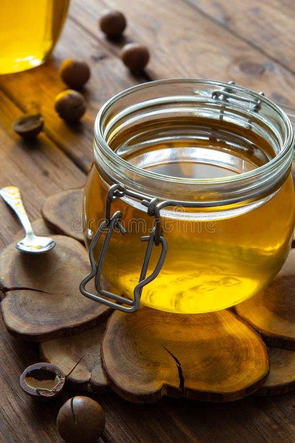 Ghee or clarified butter in a jar on a wooden stand on a wooden table. The composition is complemented by a small spoon and macadamia nuts stock photos