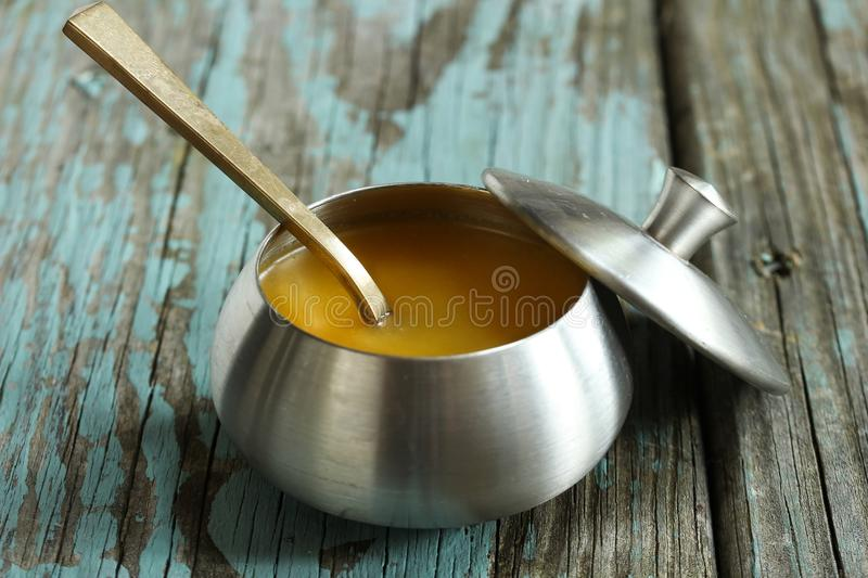 Ghee / Clarified butter on rustic blue background, selective focus. Ghee / Clarified butter on rustic blue background royalty free stock image