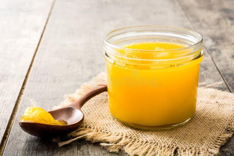 Ghee ou beurre clarifié dans le pot et la cuillère en bois sur la table en bois photographie stock libre de droits