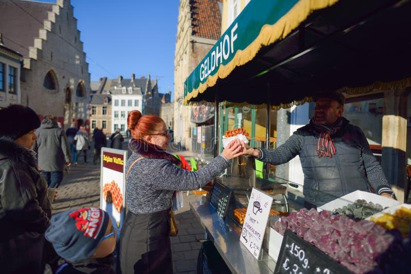 GHENT, BÉLGICA - 5 de dezembro de 2016 - mulher que compra o waffle belga nas ruas de Ghent, Bélgica imagens de stock royalty free
