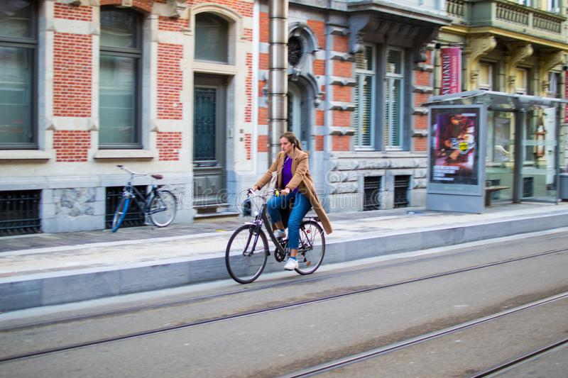 Ghent, Belgium; 10/31/2018: Panning effect photography of a woman riding on a bike through a street in the city royalty free stock photo