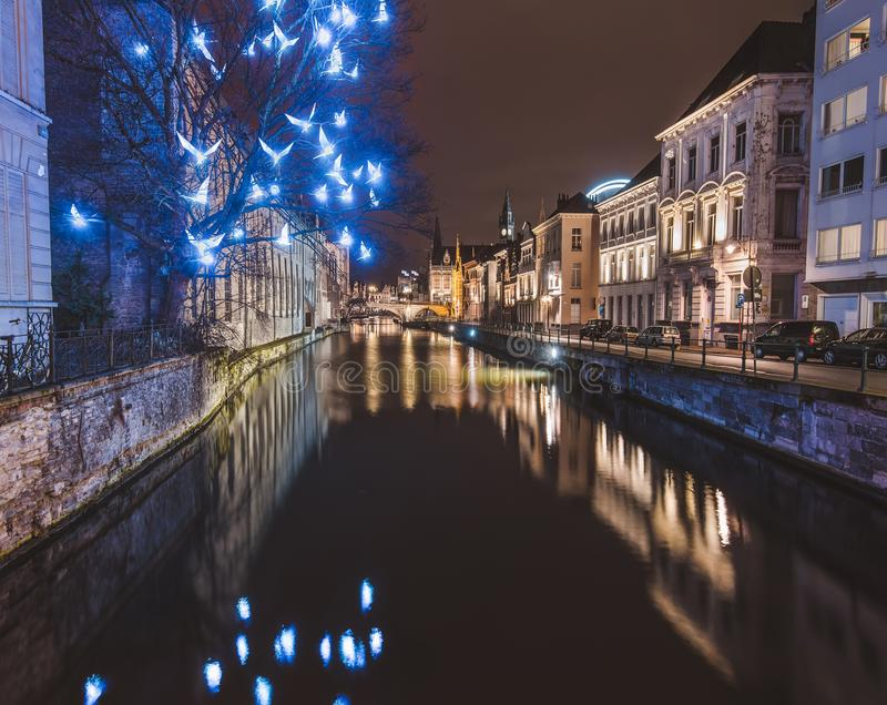 Ghent Christmas Illumination and Canal by Night. Ghent, Flanders, Belgium - January 3th, 2017. Christmas illuminated birds installation and medieval houses royalty free stock photos