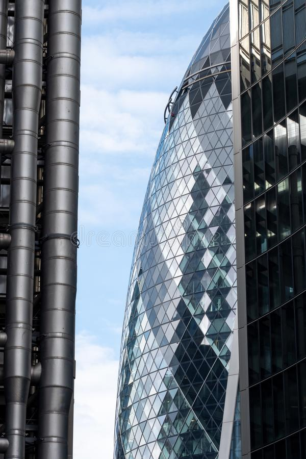 The Gherkin Building at 30 St Mary Axe in the City of London financial district, visible behind the Lloyd`s and Willis buildings. royalty free stock photos