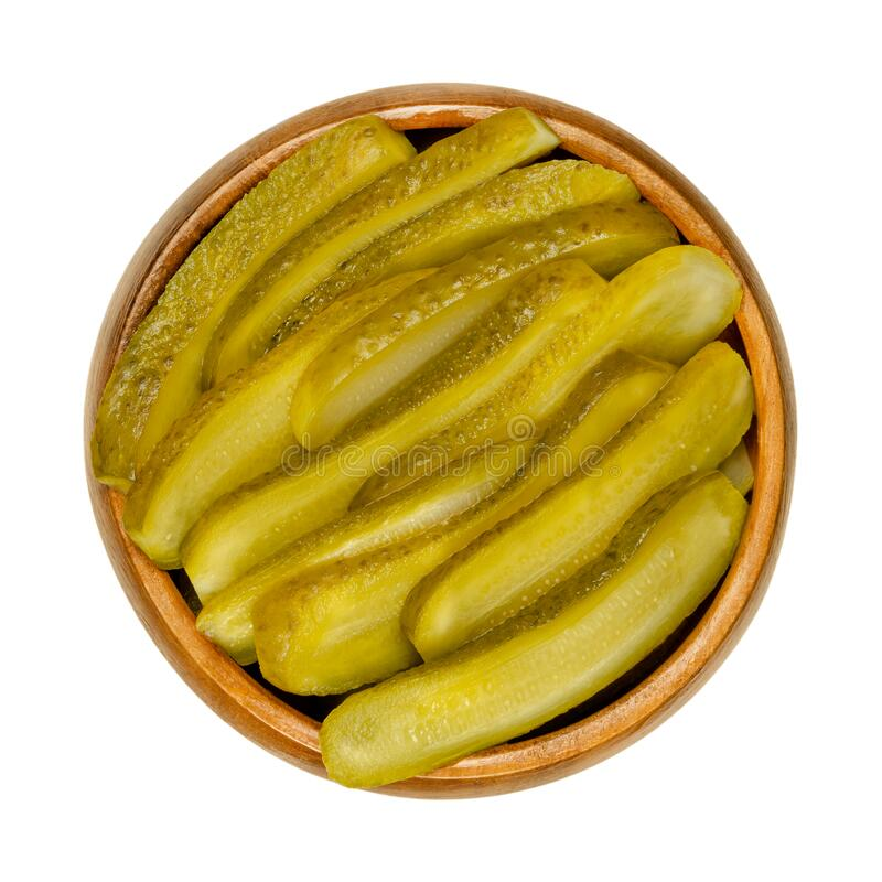 Sliced pickled cucumbers, also known as pickle or gherkin, in wooden bowl royalty free stock photos