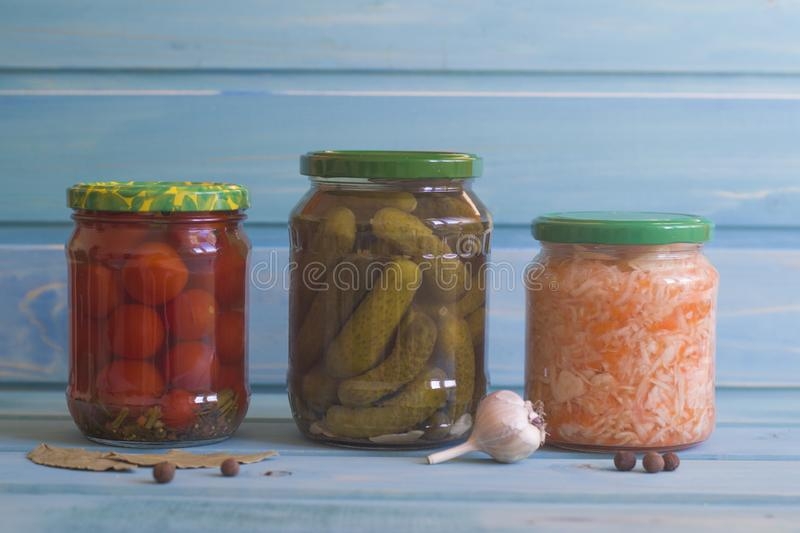 Gherkins, tomatoes and sauerkraut in jars on a blue wooden backg royalty free stock image