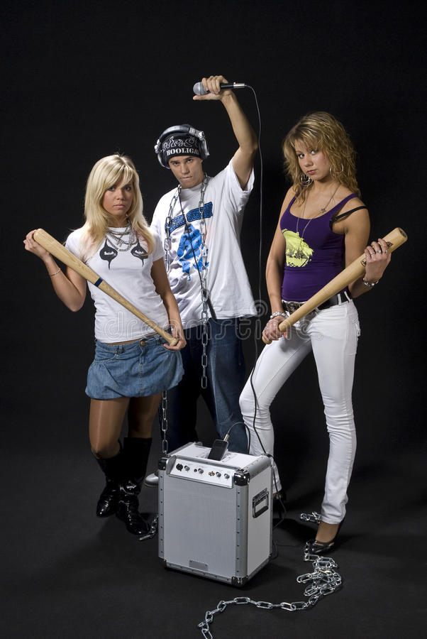 Ghetto group. Young DJ/rapper with two teen girls and his mobile sound system isolated on black background stock photo