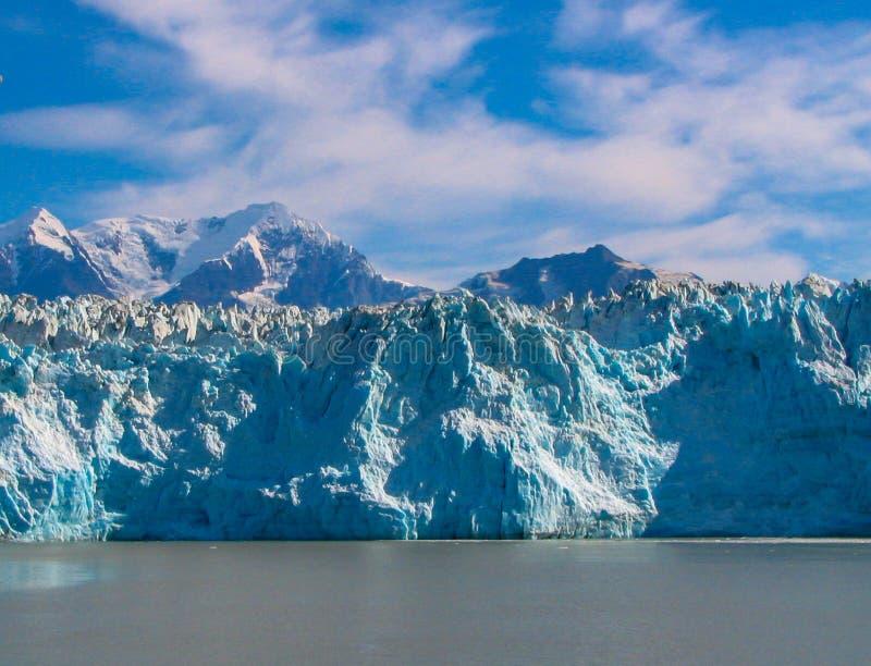 Ghiacciaio d'Alasca in acque blu con le montagne fotografie stock