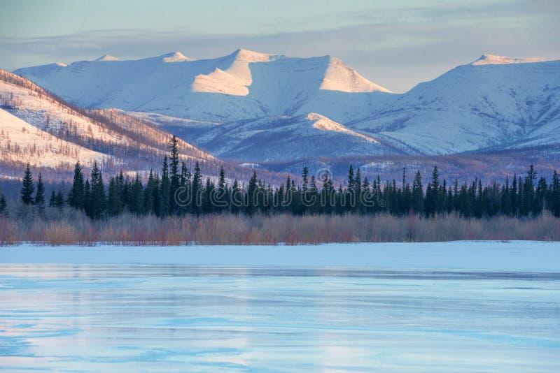 Ghiaccio blu del lago congelato alla mattina Paesaggio di inverno sulle montagne ed il lago congelato in Yakutia, Siberia, Russia immagine stock