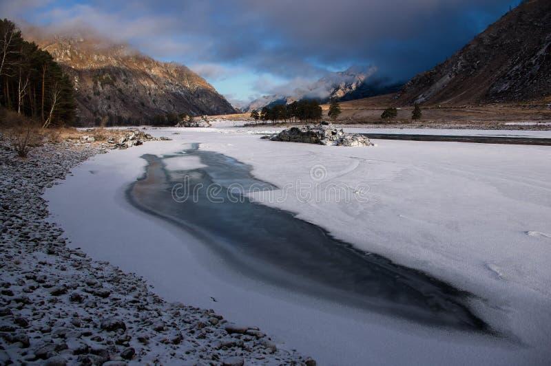 Ghiaccio-foro in fiume coperto di ghiaccio sui precedenti di un'alba variopinta e di alte rocce, montagne di Altai fotografia stock