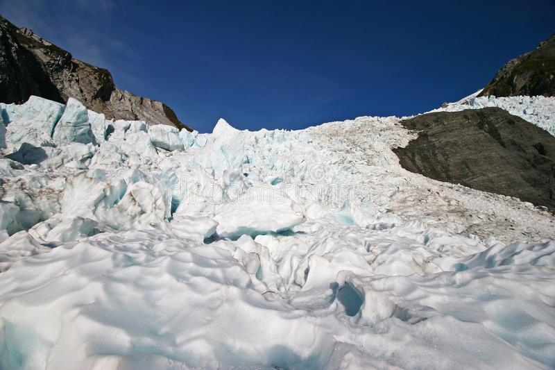 Ghiaccio ondulato del ghiacciaio davanti ai bei pezzi stracciati del ghiaccio sulla montagna fotografia stock