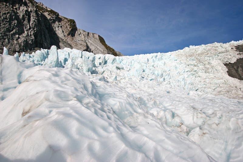 Ghiaccio ondulato del ghiacciaio davanti ai bei pezzi stracciati del ghiaccio sulla montagna fotografia stock libera da diritti