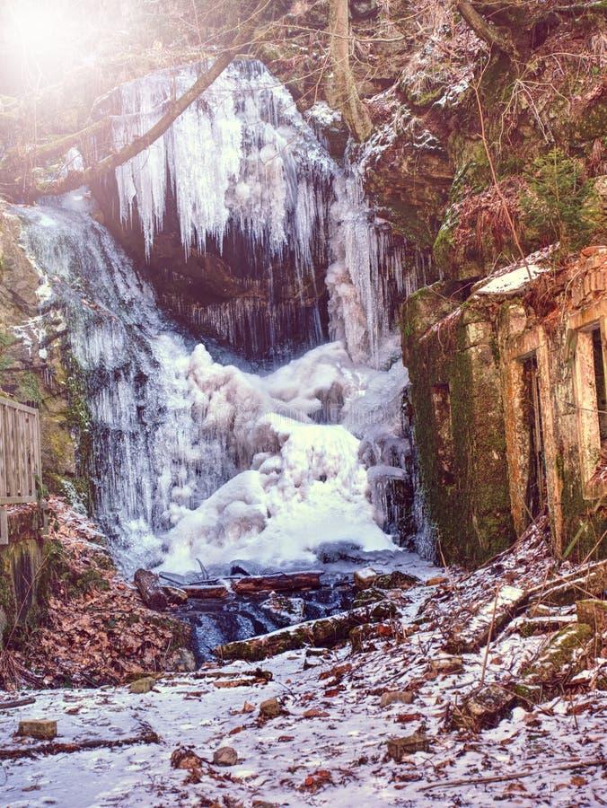 Ghiaccioli in cascata congelata Snowy e pietre e massi ghiacciati con le gocce fotografie stock