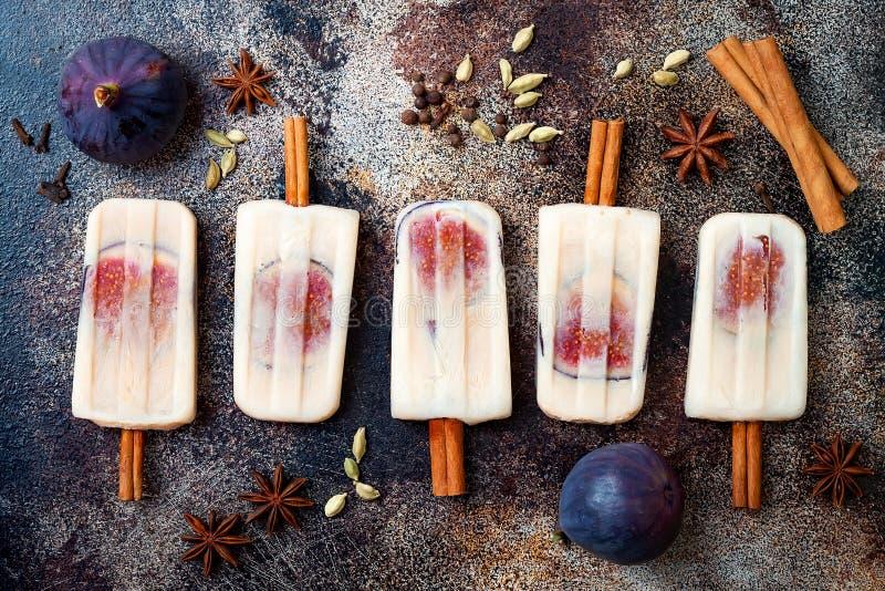 Ghiaccioli del latte di Masala chai con i fichi sui bastoni di cannella Ghiaccioli aromatizzati per la caduta, stagione invernale immagini stock