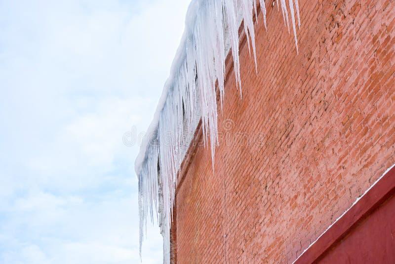 Ghiaccioli lunghi sul tetto di una casa contro un fondo del muro di mattoni immagine stock