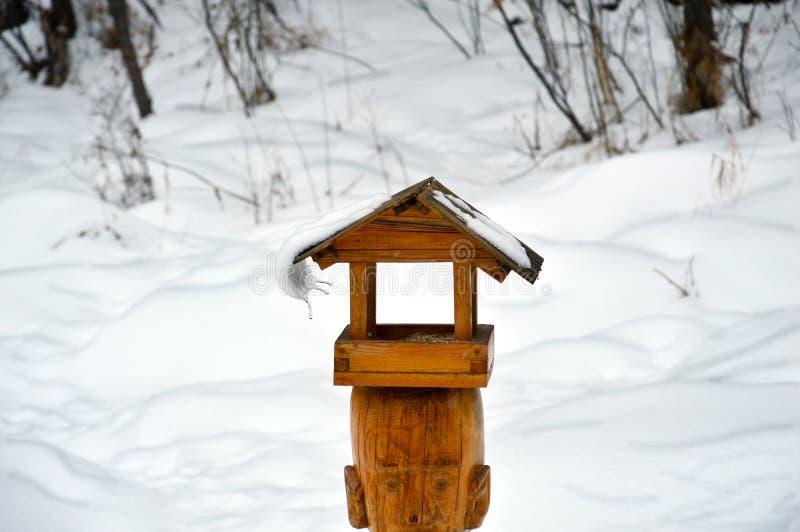 Ghiacciolo curvo che pende dal tetto dell'alimentatore dell'uccello Il presagio della molla immagine stock libera da diritti