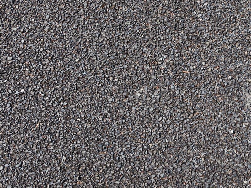 Ghiaia scura sulla strada non asfaltata fotografia stock