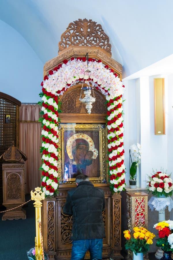 Ghighiu, Rumänien - 1. Februar 2019: Unidentifizierbarer Mann in seinen Knien betet an der towondrous Ikone von Jungfrau Maria u lizenzfreie stockbilder