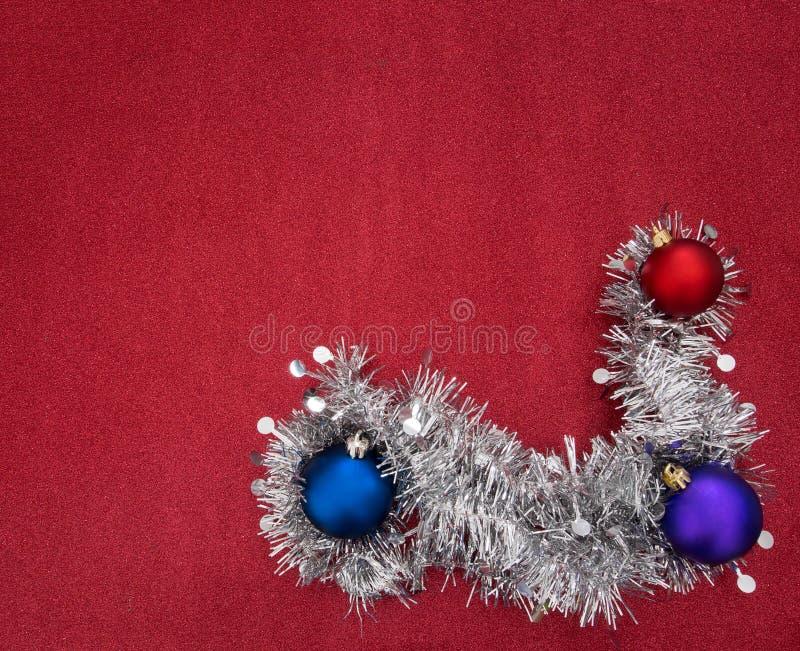 Ghirlanda del lamé e bagattelle d'argento di Natale sul festi rosso di scintillio fotografie stock libere da diritti
