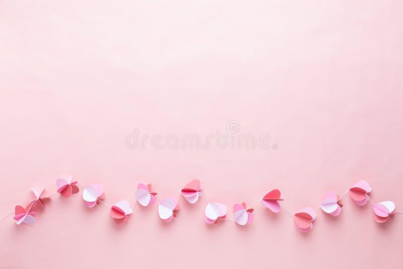 Ghirlanda di carta variopinta dei cuori sui precedenti di corallo viventi Cartoline d'auguri di Valentine Day fotografia stock libera da diritti
