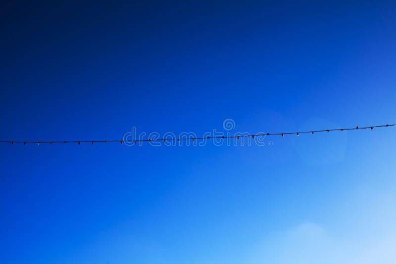 Ghirlanda elettrica lunga del cielo blu per l'accensione con le lampadine della luce bianca contro lo sfondo di chiaro cielo blu immagine stock libera da diritti