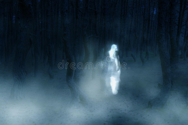 Ghost. Fake ghost photo - woman silhouette in white dress walking in the creepy forest