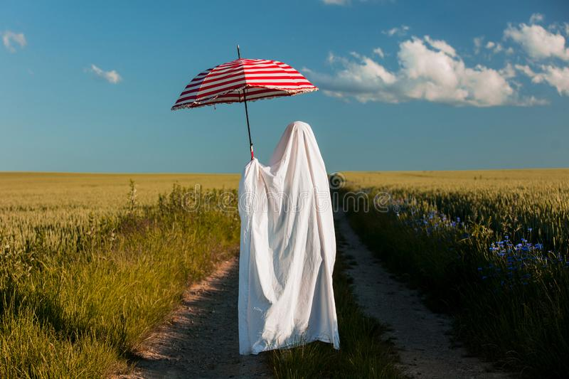 Ghost in a bed sheet with umbrella on countryside road near a wheat field. Cute ghost in a bed sheet with umbrella on countryside road near a wheat field stock images