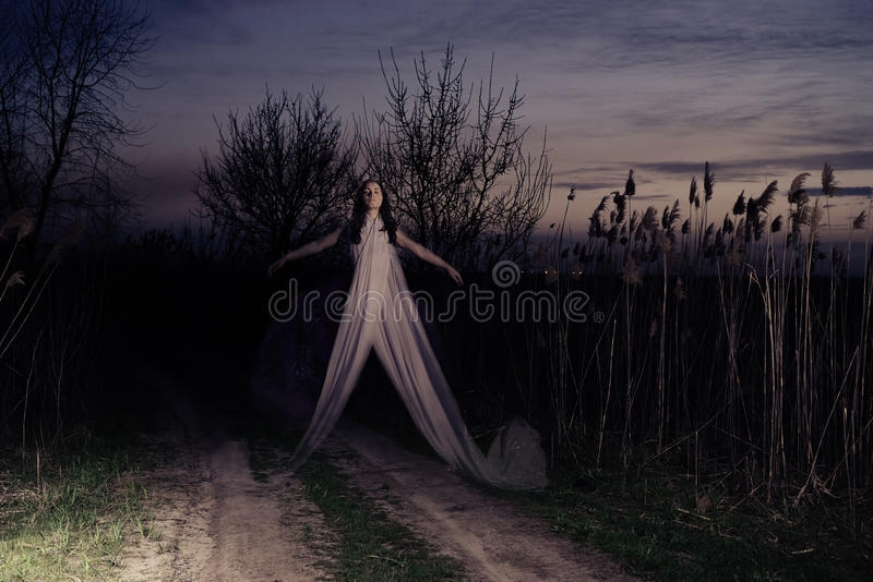 The Ghost flies along the road. Ghost on a rural road. Evening royalty free stock photo