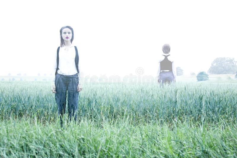 Ghost in The Fog, on the field. Mysterious woman in the Forrest. Reincarnation. Soul leaves the body after the woman`s death. Horror scene of scary. White ghost royalty free stock photo