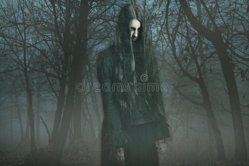 Ghost in the fog. Scary ghost of a dark girl in the fog . Horror and halloween conceptual stock photo