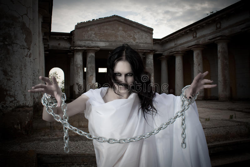 Ghost girl. Pretty brunette with arms in chains royalty free stock photography