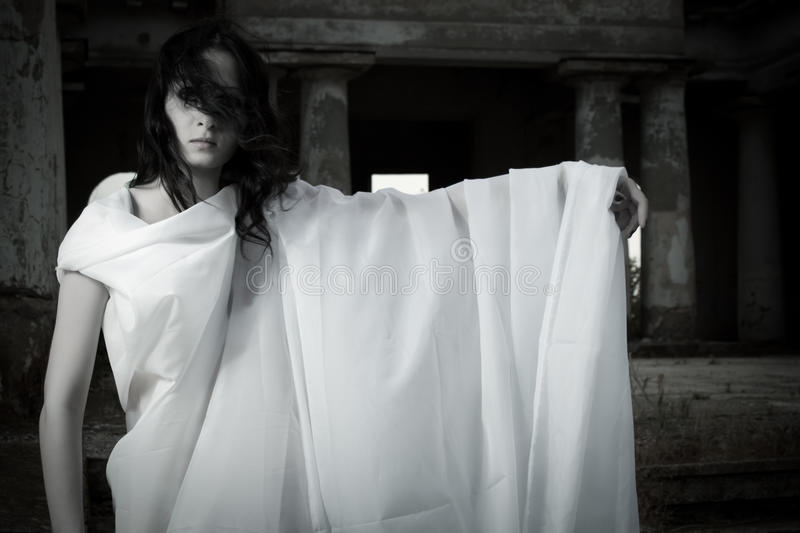 Ghost girl. Pretty girl in white clothes on an old cemetery royalty free stock photos