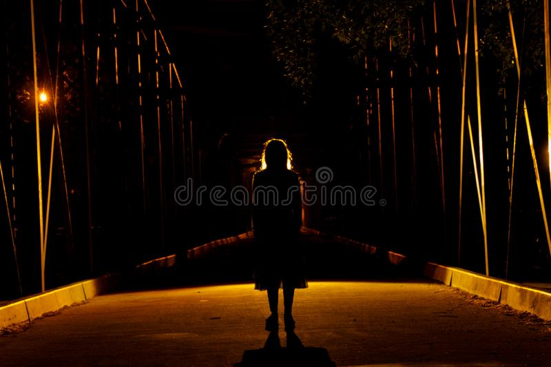 Ghost girl in the darkness. Terrifying image of a girl on a bridge during halloween stock images