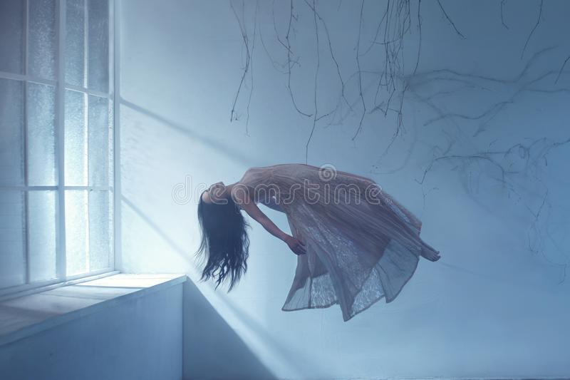 A ghost girl with long hair in a vintage dress. A photograph of levitation resembling a dream. A dark Gothic room with royalty free stock photography