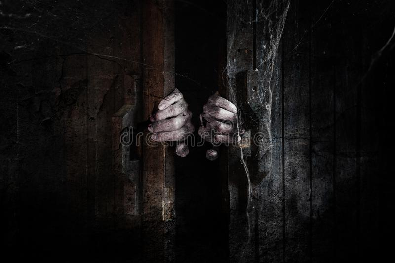 Ghost hands open the wooden door from the inside of the old dark room. royalty free stock image