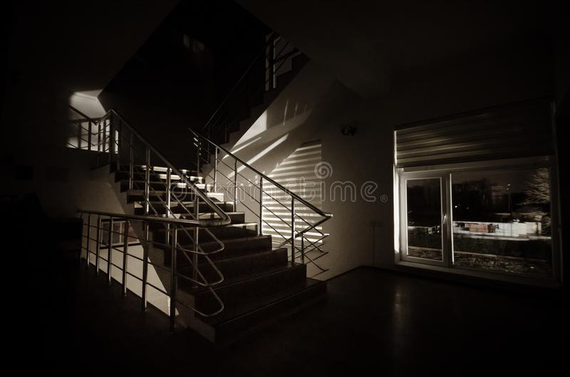 Ghost in Haunted House at stairs, Mysterious silhouette of ghost man with light at stairs, Horror scene of scary ghost spooky llig. Hts . Scary hall. Halloween stock image