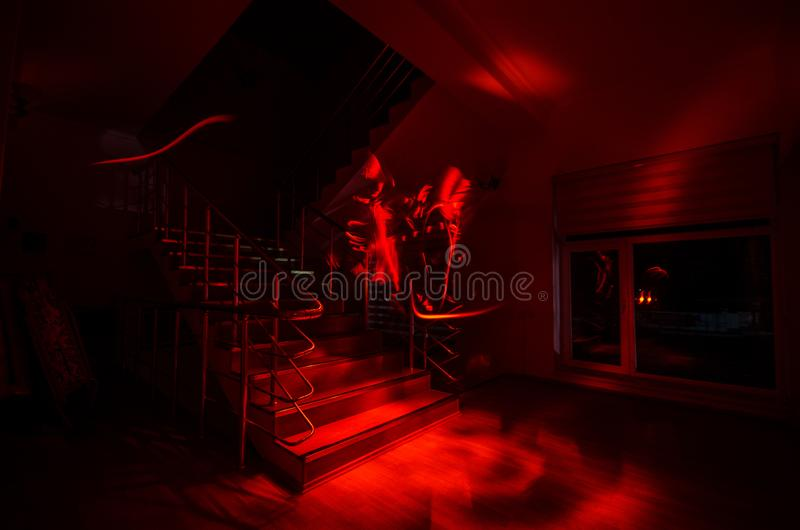 Ghost in Haunted House at stairs, Mysterious silhouette of ghost man with light at stairs, Horror scene of scary ghost spooky llig. Hts . Scary hall. Halloween royalty free stock photo