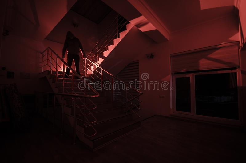 Ghost in Haunted House at stairs, Mysterious silhouette of ghost man with light at stairs, Horror scene of scary ghost spooky llig royalty free stock image
