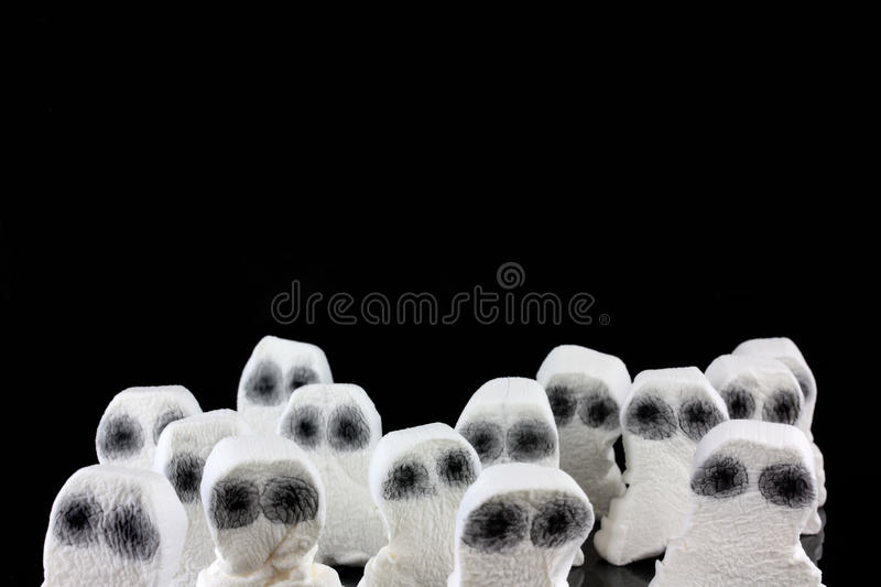 Ghost heads in a scary crowd. On a black background stock photo